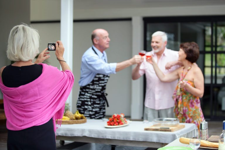 Older woman taking a photo at a party